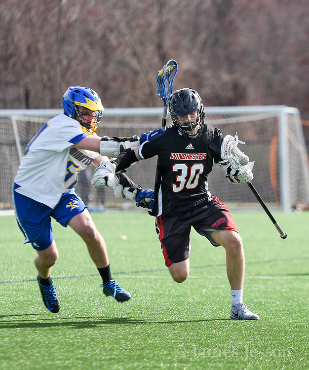 Winchester High School junior Harris Carpini moves the ball up the field under pressure from Lexington High School senior Uri Lurie during the game in Lexington, April 24, 2018. Winchester won the game, 11-6.   [Wicked Local Photo/James Jesson]