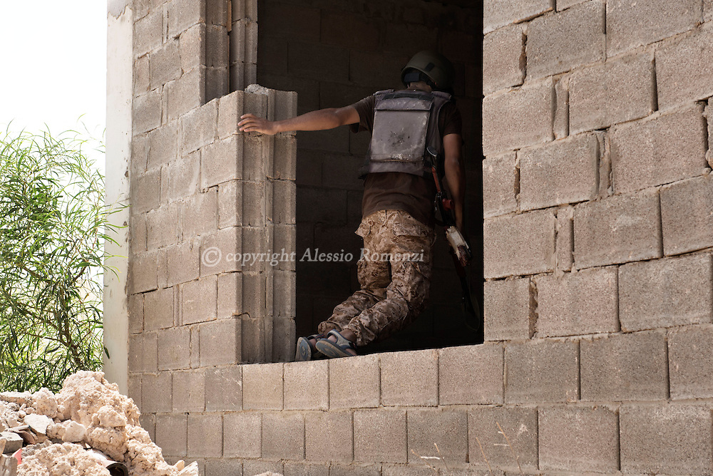 Libya: a fighter affiliated with Libya's Government of National Accord's (GNA) jumps inside a house as he is advancing in 700 neighbourhood in Sirte still under ISIS control. Alessio Romenzi