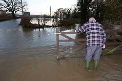 © Licensed to London News Pictures. 01/12/2015. Welshpool, Powys, Wales, UK. A man opens his gate in the hope of driving his car out as the flood water recedes. The river Severn bursts it's banks at Welshpool and causes extensive flooding. Photo credit: Graham M. Lawrence/LNP