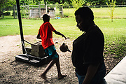 "LOWNDES COUNTY, AL – JULY 10, 2017: Deandrew, 13, plays basketball barefoot in the backyard where sewage from a nearby lagoons often spills over and contaminates the property. His aunt, Steviana, (right) said he's not supposed to play without shoes. ""Sometimes the stench is so bad, we can't go outside,"" Steviana said. ""It's like we're prisoners in our own home."" Along with roughly one in three individuals tested in a recent study conducted by Baylor, Deandrew tested positive for hookworm.<br /> <br /> A recent study conducted by Baylor University suggests that nearly one 1 in 3 people in Lowndes County have hookworm, a parasite normally found in poor, developing countries. Below ground septic tanks are common in Lowndes, but due to the chalky clay soil throughout much of the Black Belt, septic tanks are prone to backing up into people's homes during heavy rains. With failing or absent municipal sewage systems in the county, many families choose to live with open, above ground sewer systems made from PVC pipe, which pump raw sewage into nearby streams or open land."