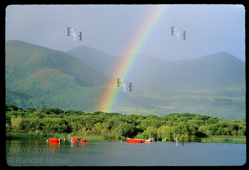 Early morning rainbow arches over mountains, Ross Island and red motorboats on Lough Leane in Killarney National Park, Ireland.