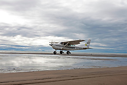 Cessna U206G (registration N1749R) single engine prop plane takes off from a sandy beach, Lake Clark National Park, Alaska, United States of America