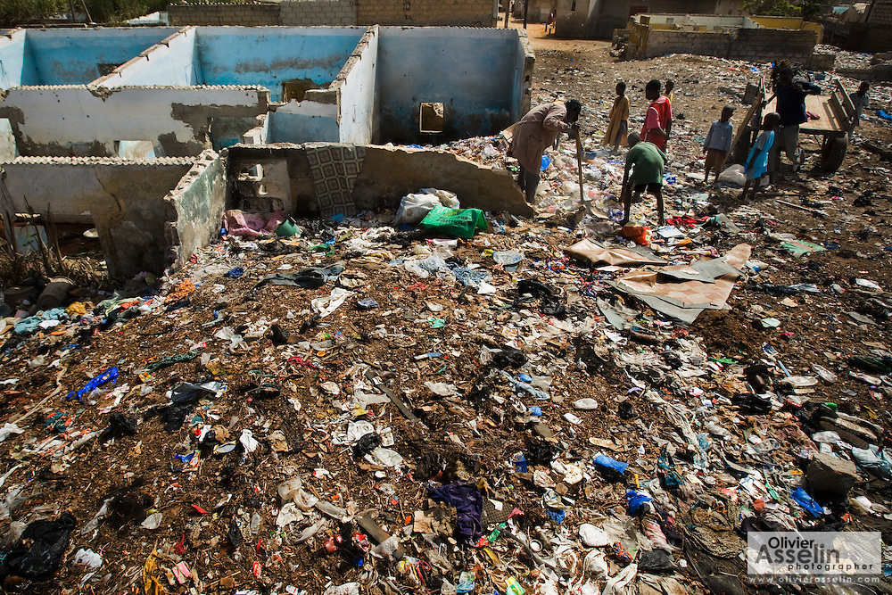 Boys spread garbage inside a home that was damaged by flooding to raise the floor and soak up sitting water in the Medina Gounass neighborhood of Guediawaye, Senegal on  Friday May 1, 2009. (Olivier Asselin for the New York Times)