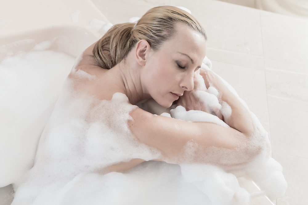 Portrait of sensual woman relaxing in a bathtub Spa.