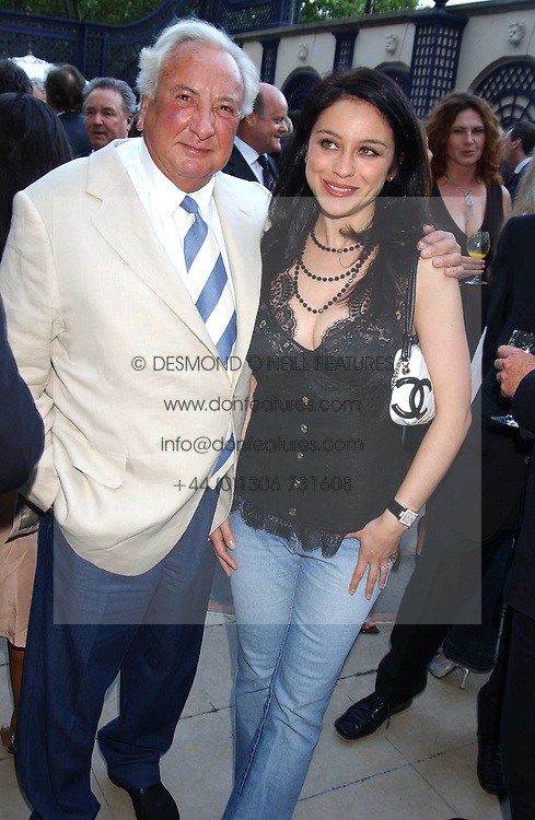 MICHAEL WINNER and PAOLA LOMBARD at a party hosted by Andrew neil and The Business Newspaper held at The Ritz, Piccadilly, London on 12th July 2005.<br />