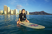 Boy on surfboard, Waikiki Beach, Waikiki, Oahu, Hawaii, USA<br />