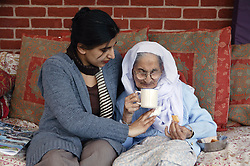 Granddaughter sitting with her Sikh elderly grandmother drinking tea,