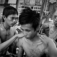 Nakhon Chai Si district, February 2010, Wat Bang Phra Temple. Monk doing tattoo on the back of a Thai pious Bouddhist inside a temple, in Nakhon Chai Si district, Thailand, about 50 km west of Bangkok. The temple is famous for its monks and their practice of giving Sak Yant tattoos with wooden bamboo and metal needless. Many believe that protective energy flows through the tattoos, keeping them safe from harm. It is not simply about getting a talisman tattoo here. The owner must activate it in order for it to serve as a lifesaving conduit. He or she must respect the precepts set by the head master.