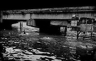 Children swim under a highway bridge in the highly contaminated waters of the Estero de Vitas right below the old Smokey Mountain garbage dump, once famous for its smoke generated by spontaneous combustion in the refuse.  Families, on the right, have built makeshift shacks under one of the bridges just above the river's surface, which is vulnerable to storm surges from the numerous typhoons that lash Manila every year, flash flooding during tropical downpours and tsunami in this seismically active region.  Climate change will intensify tropical storms, and raise the sea level, bringing this contamination back up onto the congested streets of Manila.  Tondo District, Manila, Philippines.<br /> <br /> In addition, these waters carry human waste, including antibiotic resistant bacteria, even heavy metals into Manila Bay.  It is hard to imagine a less healthy place to live and swim.
