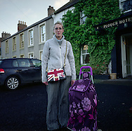"""'Woman with a Union Jack bag, Town Yetholm, 2014' from 'A Fine Line - Exploring Scotland's Border with England' by Colin McPherson.<br /> <br /> A woman with a Union Jack bag waiting for a bus before going to nearby Kelso to shop. """"People think the bag represents my politics, but really, I just liked it'"""" she said.<br /> <br /> The project was a one-year exploration of the border between the two historic nations, as seen from the Scottish side of the frontier.<br /> <br /> Colin McPherson is a photographer and visual artist based in north west England. In 2012 he was one of the founding members of Document Scotland, a collective of four Scottish documentary photographers brought together by a common vision to witness and photograph the important and diverse stories within Scotland at one of the most important times in our nation's history.<br /> <br /> 'A Fine Line' will be shown for the first time in public at Impressions Gallery, Bradford, from July 1 until September 27, 2014 to coincide with the Scottish Independence referendum."""