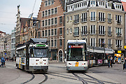 Two De Lijn trams travel along the Ghent tramway network in central Ghent, Belgium.  The tram on the left is route 4 to Zwi jnaarde, the tram on the right is route 1 to Flanders Expo. De Lijn have recently developed new modern trams (tram on right) which use 20% less electricity and are a more sustainable transport.