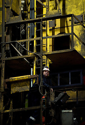© Licensed to London News Pictures. 18/04/2012..SSI Steel, Teesside, England..A steel worker looks on as he waits for the first slab of steel to come through the cutting machine...Two years after the closure of the Corus steel production plant, the huge blast furnace on the site in Teesside was re-lit at the weekend as the process of bringing the furnace back to operating temperature begins...Today, the furnace, now owned by the Thai company Sahaviriya Steel Industries saw the first steel slabs come out of the furnace. ..The steel will now be shipped direct to SSI in Thailand for use in the car or white good industries...Photo credit : Ian Forsyth/LNP