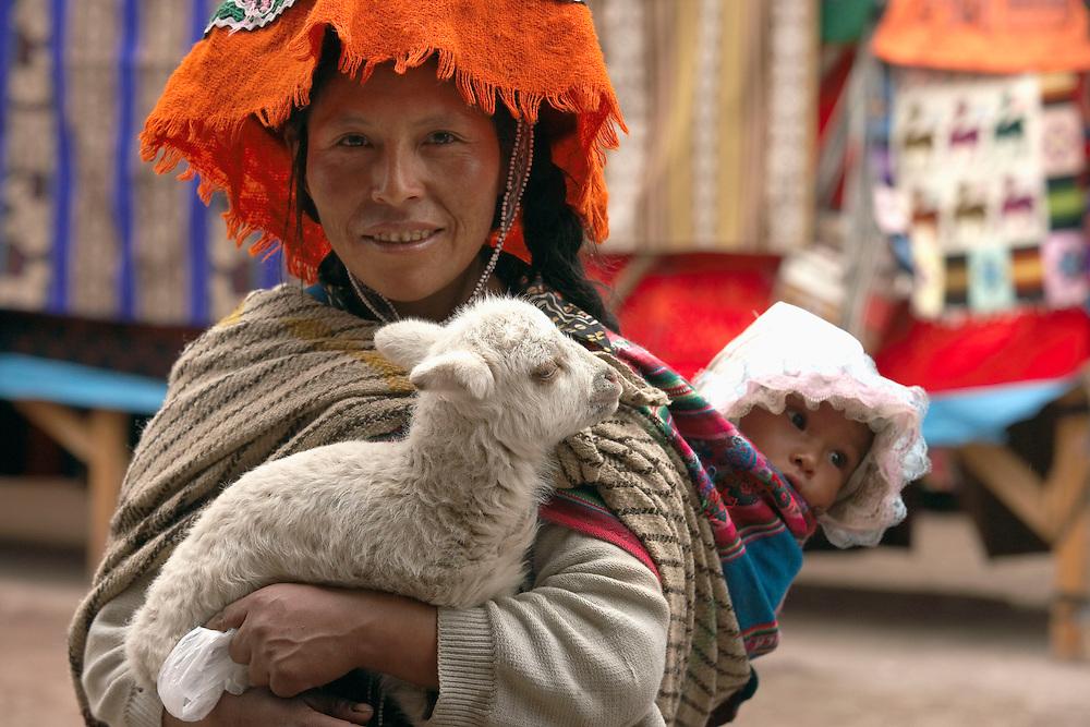 Woman, baby and baby llama at Pisac market  Pisac, Peru