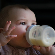 A ten month old baby girl peering out of the window while feeding herself with a bottle of milk. Photo Tim Clayton