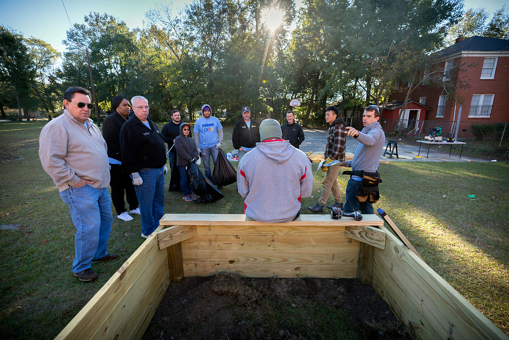 NOVEMBER, 17, 2017 - NORTH CHARLESTON, S.C. - United Way Day of Caring volunteers listen to Metanoia Project Manager Duncan Cheney, right, give instructions on building three landscaping beds on the playground near the academy in North Charleston. (BNG/Stephen B. Morton)