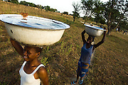 Girls carry water containers they filled from a water pump outside their village.