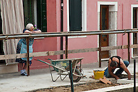 Signora watching the workman fix the sidewalk.