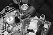 Die Pflegmutter RIN, 32 Jahre alt, .hat aus drei verschiedenen Medikamenten einen Cocktail gemischt. Mit einer Spritze zieht sie ihn auf um die Medizin einem der Kinder in den Mund geben zu können..Davor hat sie eine Kapsel aufgemacht und fuellte den Inhalt in einen Plastikbecher. Die Kapseln sind fuer die Kinder aus BAAN GERDA zum Schlucken zu gross. Die Tablette hat sie mit einem Moerser zu einem Pulver verrieben..Damit die Kinder die Medizin aufnehmen koennen, wird sie in Wasser aufgeloest, so dass es die Kinder trinken koennen oder wenn sie noch zu klein sind, wird es mit einer Spritze in den Mund eingegeben. Provinz Lop Buri, Thailand.Medikament: gelbe Kapseln  Efavirenz..Forstermother RIN, age 32, .has mixed a cocktail with three different medicines. Now she pulls the cocktail in a syringe. So she can easily give it to the childern through their mouth..She opened a capsule of EFAVIRENZ drug. The capsule is to big to swallow by the children. Therefor the powder has to be filled in a cup and dissolve in water. So that the kids can drink it easily. Tabletts had to be smashed to powder..Province Lop Buri, Thailand......
