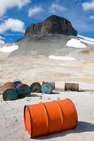 Fuel drums abandoned by miners and left to rust and leak into the wilderness watershed of Salal Creek, The Elephant, or sometimes called The Black Molar 2314 m (7592 ft) is in the distance. Coast Mountains British Columbia