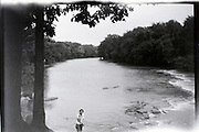person standing by river 1920s USA