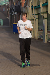 """© Licensed to London News Pictures . 24/09/2013 . Brighton , UK . ALASTAIR CAMPBELL jogs along Brighton seafront this morning (Tuesday 24th September 2013) wearing a t-shirt that reads """" Hated by the Daily Mail """" and signed by himself , Tony Robinson , Charlie Falconer . Day 3 of the 2013 Labour Party Conference in Brighton . Photo credit : Joel Goodman/LNP"""
