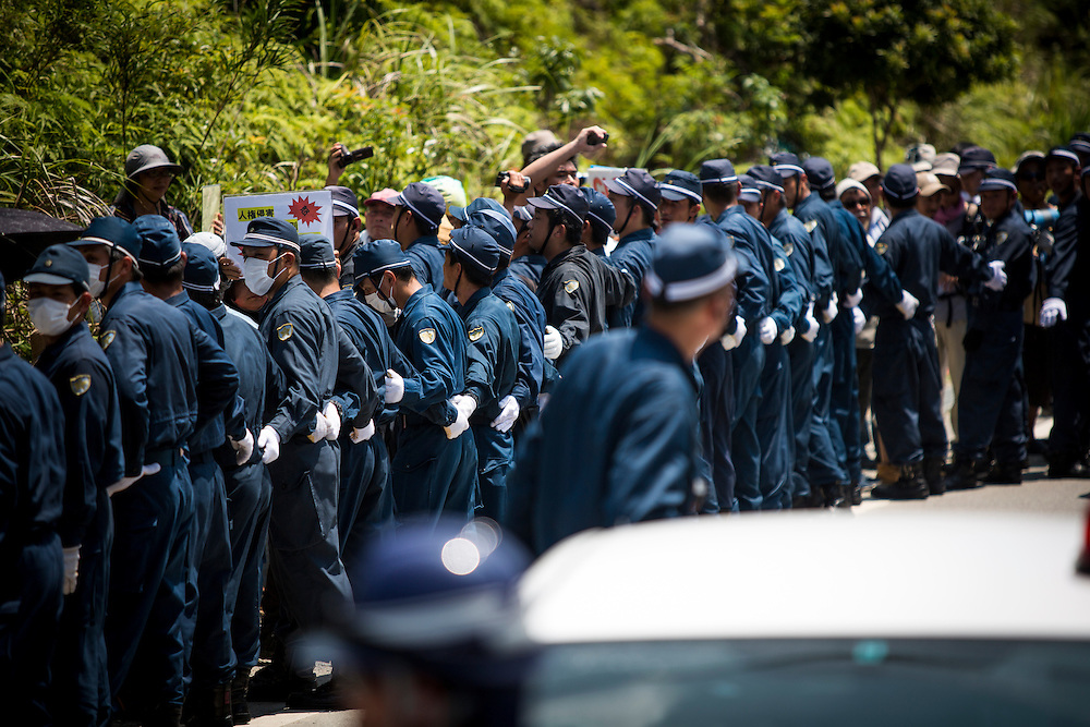 OKINAWA, JAPAN - AUGUST 19 : Police is seen to guard the Anti U.S base protesters as they staged a protest against the construction of helipads in front of the gate of U.S. military's Northern Training Area in the village of Higashi, Okinawa Prefecture, on August 19, 2016. Japanese government resume construction of total six helipads in a fragile ten million year old Yanbaru forest that is home to endemic endangered species such as the Okinawan rail and Okinawan wood pecker. (Photo by Richard Atrero de Guzman/NURPhoto)