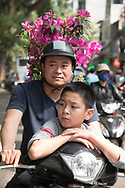 A father and son carrying an azalea plant on the back of their motorcycle in Hanoi, Vietnam, Southeast Asia
