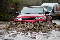 © Licensed to London News Pictures. 06/03/2019. Leeds UK. Car's struggle through flood water in Leeds this morning. Heavy rain last night has caused flooding in Leeds this morning leaving cars abandoned in flood water on Knowsthorpe Lane in the Cross Green area of the city. Photo credit: Andrew McCaren/LNP