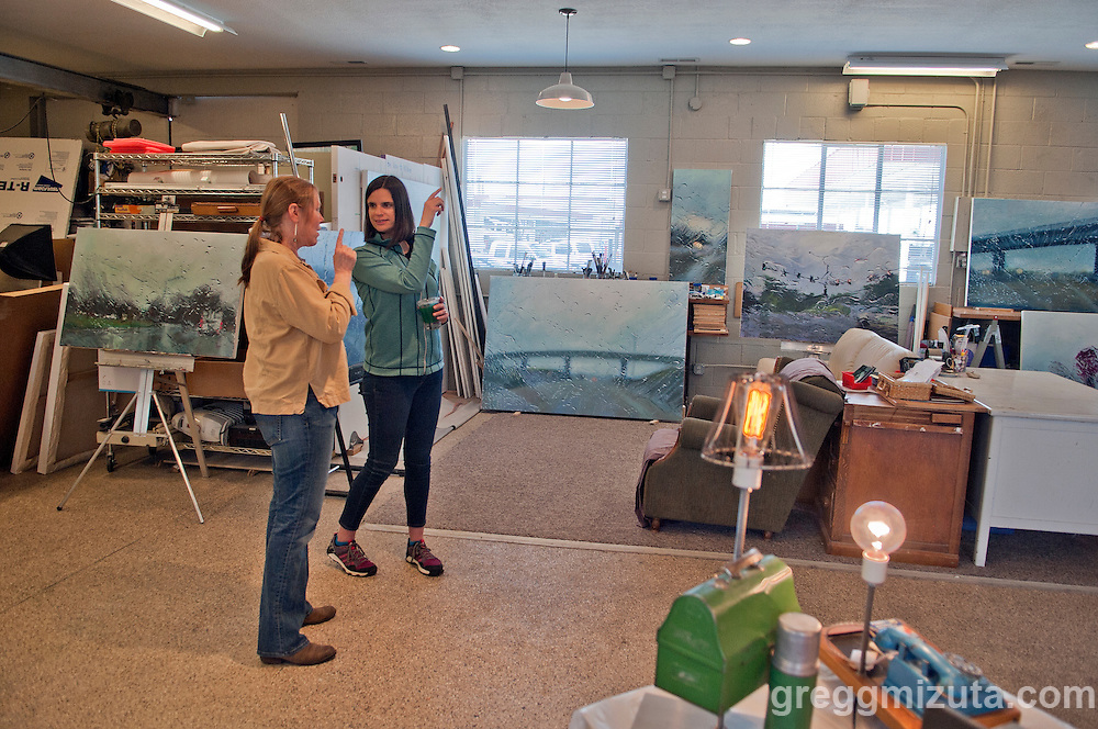 Artist Karen Woods talks to Danielle Casazza Hurd. In the background of her studio are paintings in her &quot;The Way to Wilder&quot; series. The series will be on exhibit at the Boise Art Museum May 21 &ndash; September 11, 2016.<br /> <br /> Karen's shared studio w/Geoffery Krueger, Gina Phillips, and Hindi Morland, was one of the venues on Jodi Eichelberger's ST(r)EAM Bike/Art tour through the Surel Mitchell Live-Work-Create District in Garden City, Idaho on April 30, 2016.<br /> <br /> Artists and venues on the tour included Surel's Place, Megan Levad, Sara Hill, Will Bennett, Victor Myers and Corridor Surf Shop, Geoffery Krueger, Karen Woods, Gina Phillips, Hindi Morland, Heidi Haislmaier and the new Telaya Winery where Segreto Wood Fired Pizza set up shop for the bike tour group.