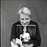 A smiling middleaged woman holding a picture of David Bowie