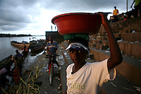A boy carries a bucket of cut sugar cane on his head at the market dock on the Atrato River in Quibdo, the capital of the state of Choco, on October 6, 2006. Choco is a state that has suffered terribly at the hands of both rightwing paramilitaries and leftist rebels over the years, causing many to flee to other parts of Colombia. The Choco is located on the Pacific coast of Colombia and most of the people are black descendants of African slaves. (Photo/Scott Dalton).