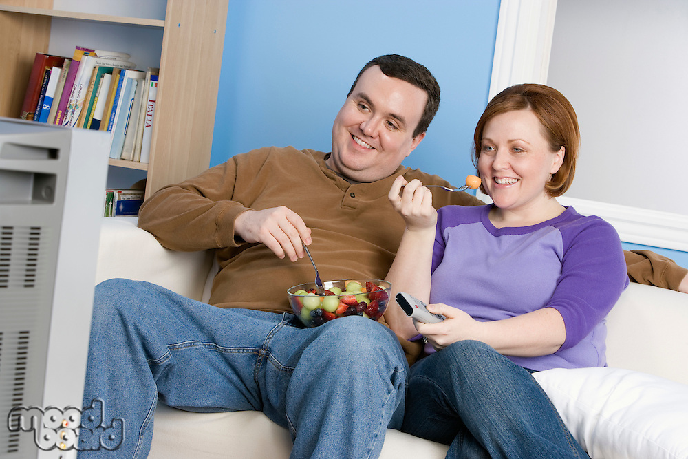 Overweight couple eating fruit on sofa