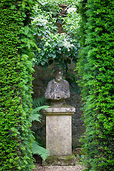 View through yew arch towards statue in the White Garden at Hidcote Manor. Taxus baccata