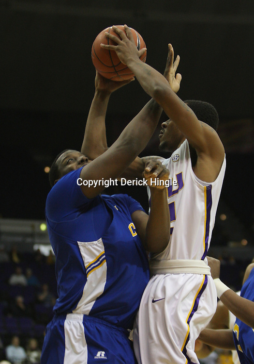 Jan 04, 2010; Baton Rouge, LA, USA; LSU Tigers guard Aaron Dotson (12) collides with McNeese State Cowboys forward Will Morning (1) during the first half at the Pete Maravich Assembly Center.  Mandatory Credit: Derick E. Hingle-US PRESSWIRE