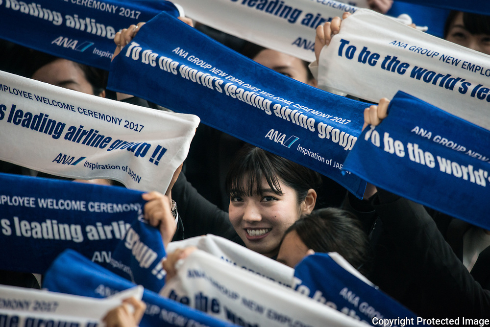Newly hired employees hold up banners for a group photograph during the welcome ceremony of ANA Holdings Inc. at the company's hanger on April 1, 2017 in Tokyo, Japan. Japanese airlines ANA Holdings welcomed 2,800 new employees, the largest number to date for the company. As the majority of Japanese start their career on April 1st after graduating from schools in February or March, it is a custom for large Japanese corporations to hold mass welcoming ceremonies for their new employees. 1/04/2017-Tokyo, JAPAN