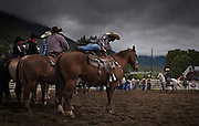 Cowboy mounts his horse while waiting to compete in the Calf Roping at the 98th Falkland Stampede in Falkland, B.C. (2016