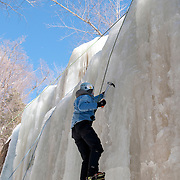 "Dan Hawes of Hanson, Massachusetts, climbs the frozen Champney Falls in the White Mountain National Forest. He uses 12 pointed crampons mounted on insulated plastic mountaineering boots, and an ice axe in each hand to aid her ascent of the waterfall. A rope attached to his climbing harness runs to an anchor at the top of the route, then down to his climbing partner and wife Jen Hawes (not shown), who guarantees that he is ""on belay: in case of a slip or fall."