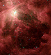 The Orion nebula, our closest massive star-making factory, 1,450 light-years from Earth. The nebula is close enough to appear to the naked eye as a fuzzy star in the sword of the popular hunter constellation. Spitzer Space Telescope.