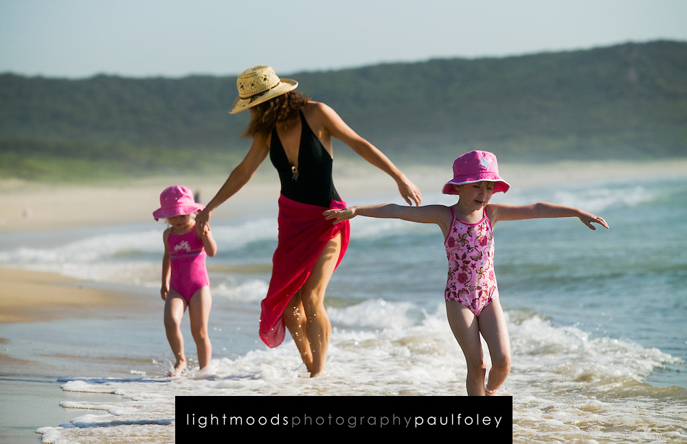 Girls and mother playing on Catherine Hill Bay Beach, near Newcastle, Australia.