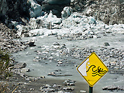 A yellow sign warns of glacier ice falling, creating a wave, and submerging a person in dangerous water, at Fox Glacier, South Island, New Zealand. As of 2012, both the Fox and Franz Josef Glaciers are more than 2.5 kilometers (1.6 miles) shorter than a century ago. Fox Glacier retreated throughout most of the last 100 years, advanced from 1985-2009, then began retreating again. In 1990, UNESCO honored Te Wahipounamu - South West New Zealand as a World Heritage Area.