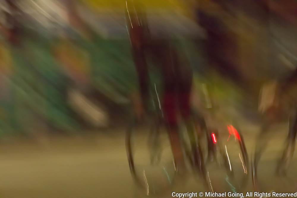 muted color palette with blurred motion of two bicycle riders at night
