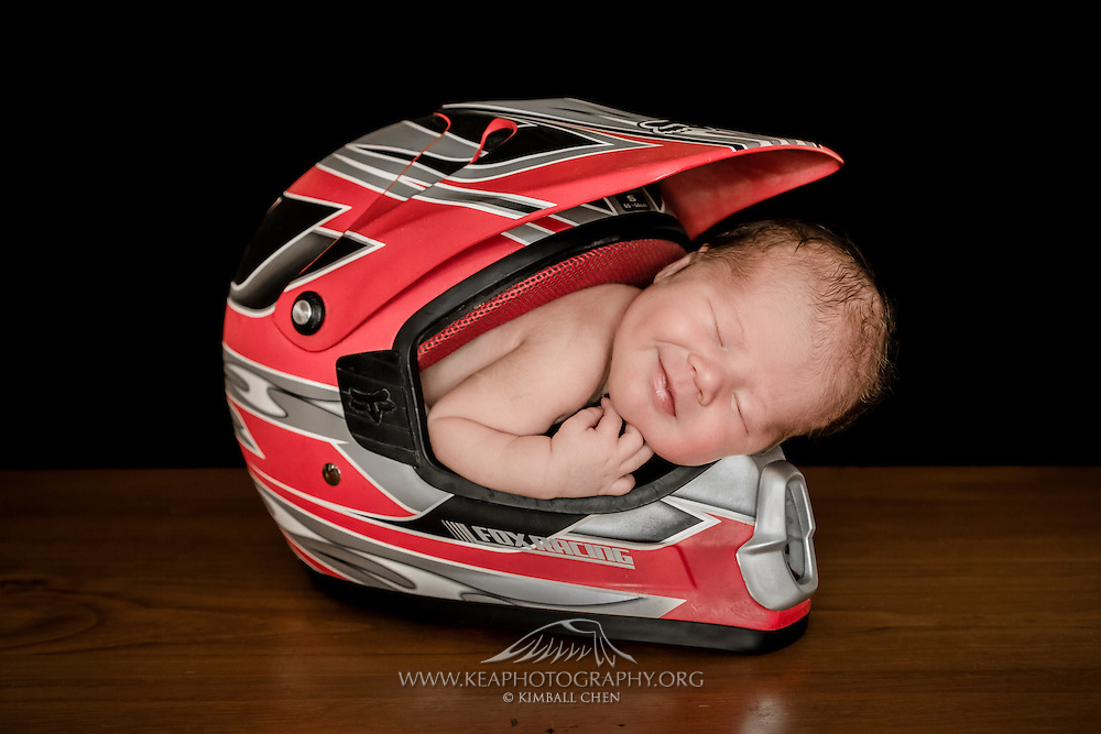 Four-day old newborn smiling in his sleep, in a dirtbiking motocross helmet.