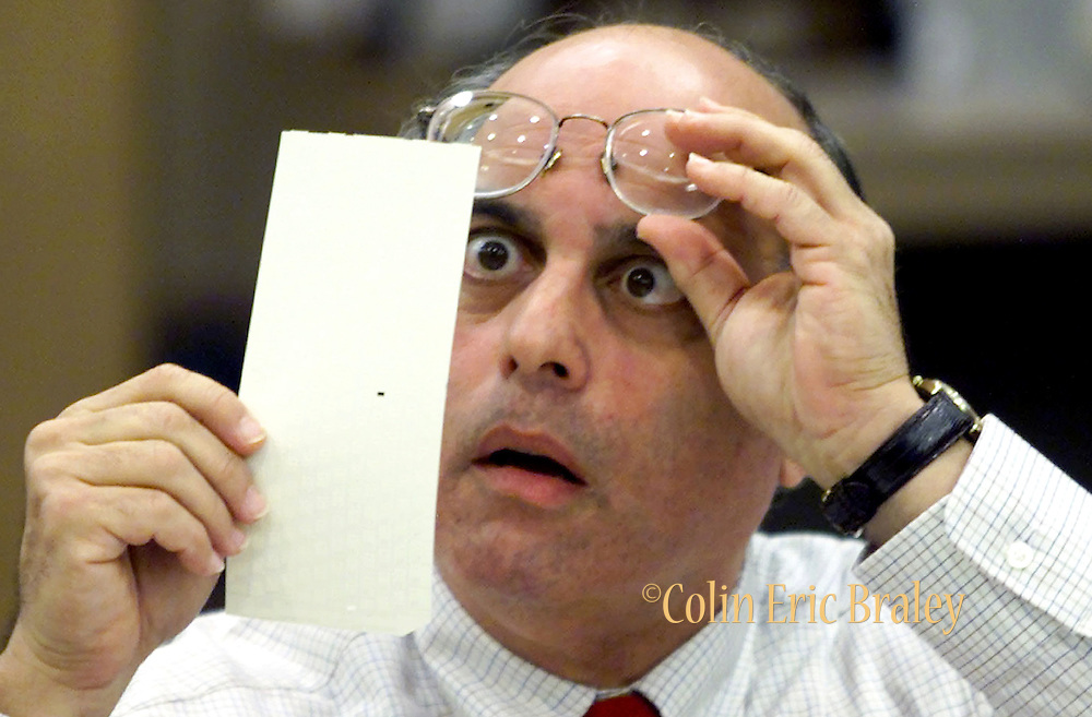 Broward County Canvassing Board member, Judge Robert Rosenberg, stares at a dimpled punchcard ballot November 23, 2000 as the board begins counting the county's ballots that were considered questionable. After review by the three member panel, the vote went to Republican presidential candidate George W. Bush. REUTERS/Colin Braley