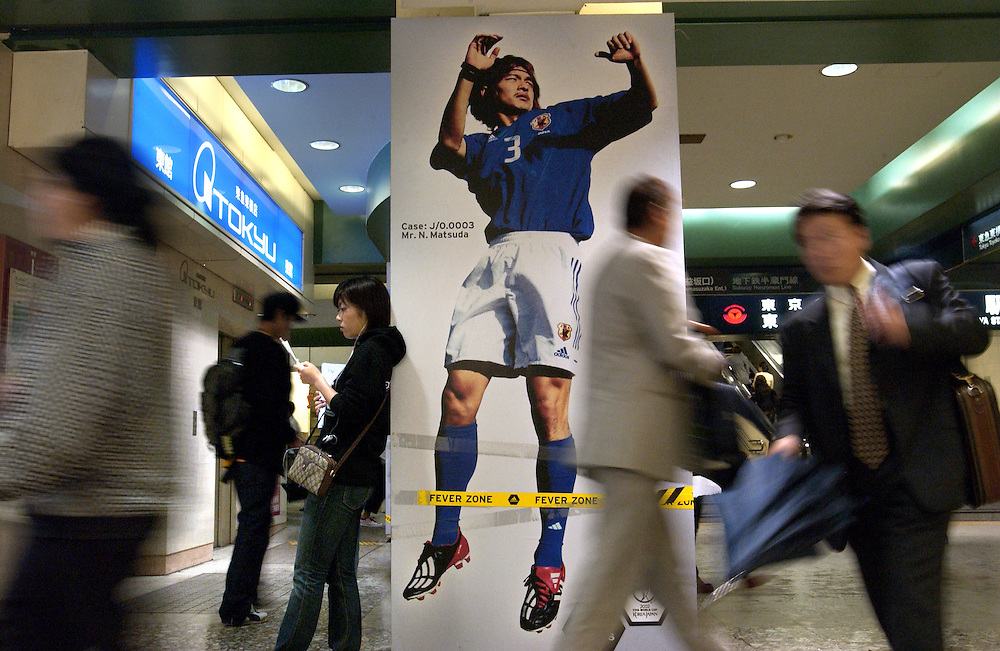 Commuters going to work at rush past a giant poster of Japan soccer star Matsuda at Shibuya Station. Tokyo Japan 27/06/02..©David Dare Parker/AsiaWorks Photography