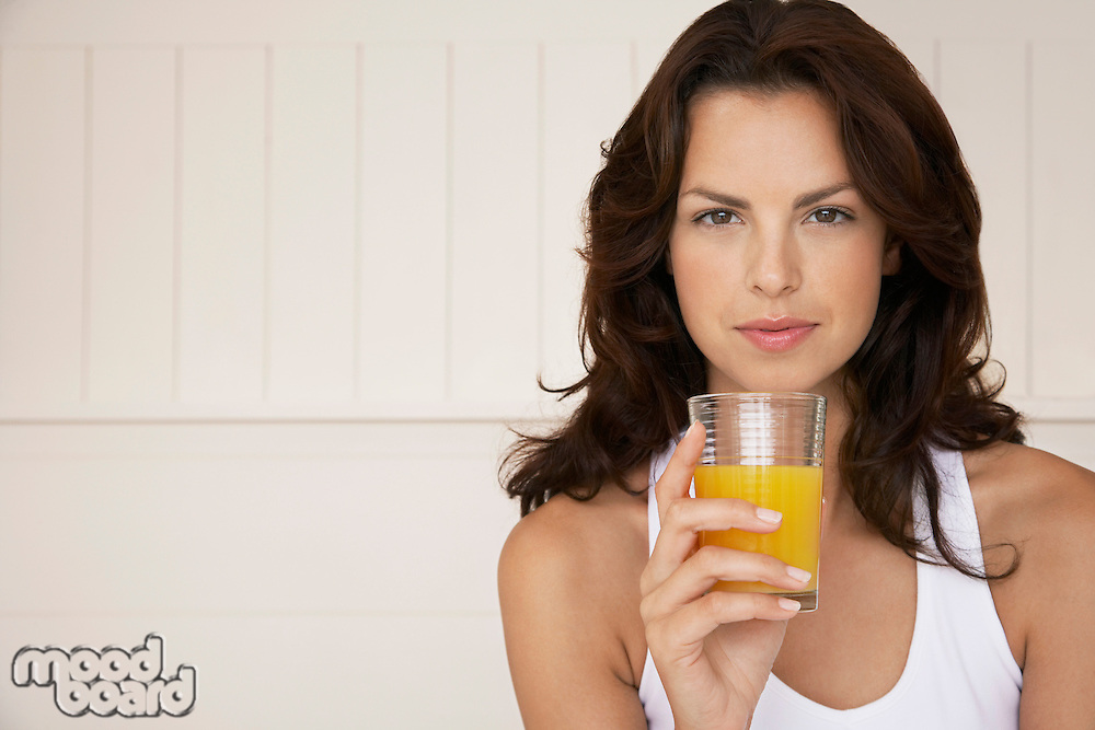 Woman drinking glass of orange juice half length