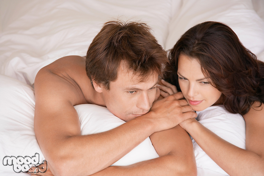 Couple lying on stomachs in bed head and shoulders