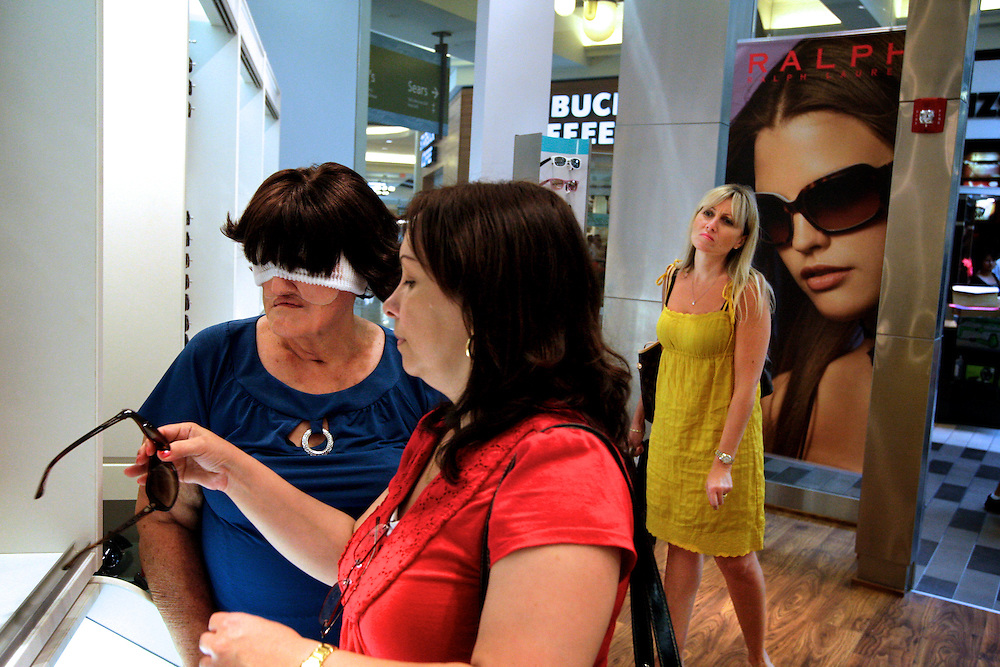 At the Coastland Center mall, Amalia Mendoza, left, is assisted by her daughter Rocio Villa, center, in shopping for new sunglasses, hoping to hide her old prosthetic face. Greg Kahn/Staff