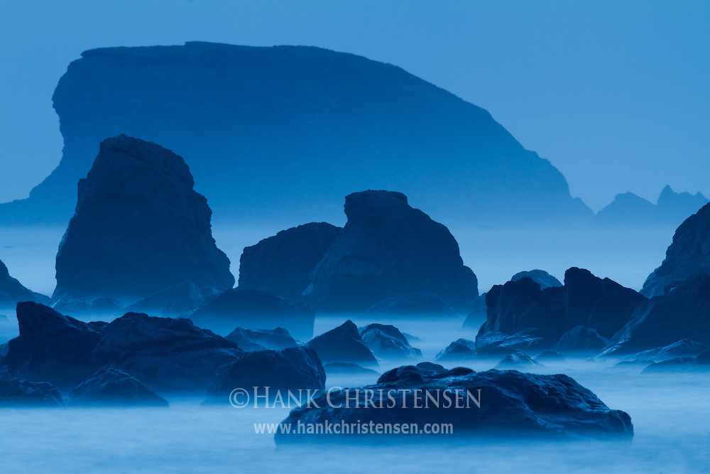 The hues of twilight cast offshore sea stacks in a blue glow as waves wash around them, Crescent City, CA