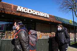 © Licensed to London News Pictures. 23/03/2020. London, UK. People wearing face masks walk past McDonald's in Haringey north London. McDonald's restaurants across the UK are to close from 7pm tonight as the spread of the coronavirus continues in the country. Photo credit: Dinendra Haria/LNP