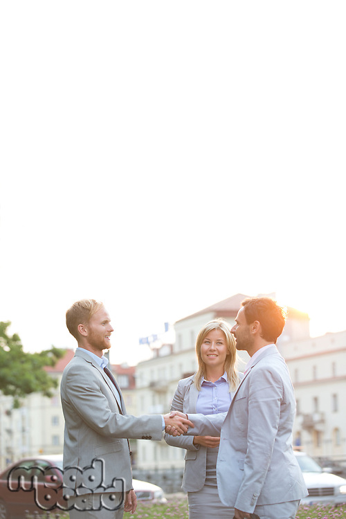 Happy businesspeople shaking hands in city against clear sky